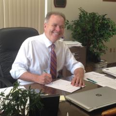 First Selectman Kevin Lyden sitting at this desk smiling.